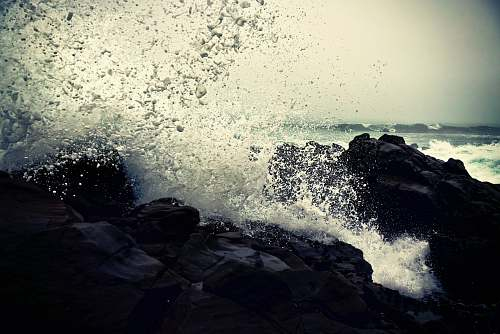 transportation grayscale photography of ocean waves crashing on rock during daytime vehicle