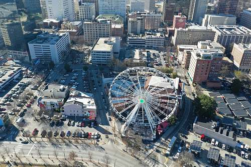 nature gray ferris wheel surround by buildings outdoors
