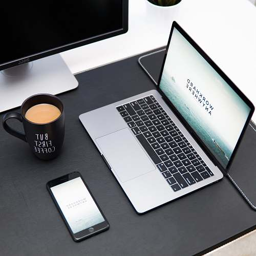 cup laptop, coffee mug, and iPhone on desk computer