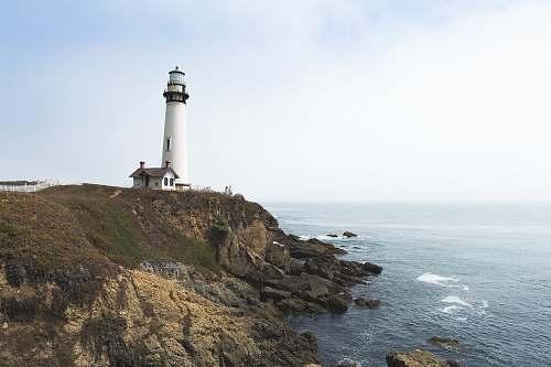beacon white lighthouse on hill near ocean coast