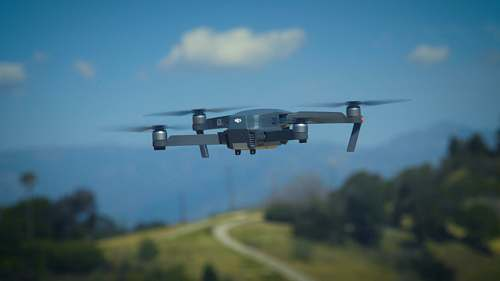 aircraft shallow focus photography of quadcopter on mid air airplane