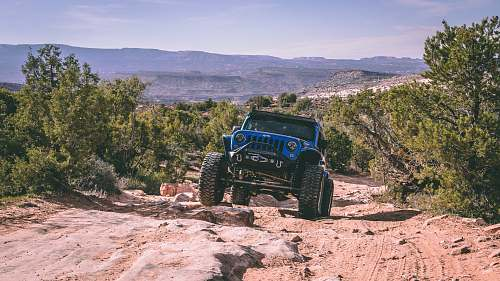 wheel blue Jeep Wrangler going up rocky sloped dirt road transportation