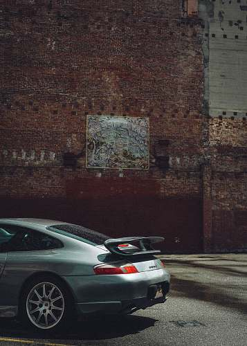 spoke silver sedan parked beside brown brick wall automobile