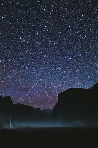 night silhouette of mountains during starry night astronomy