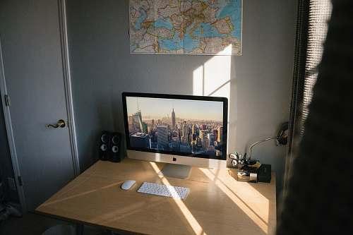 screen turned on silver iMac on beige wooden desk electronics