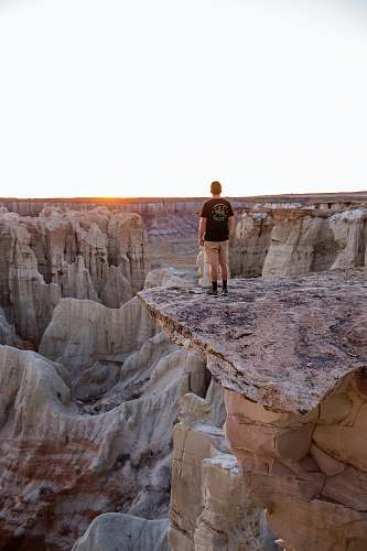 canyon man standing on mountain's edge rock