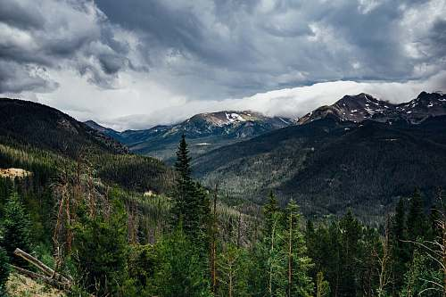 crest mountain and green tress under cloudy sky mountain range