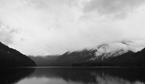 black-and-white mountain covered clouds reflecting on body of water grey