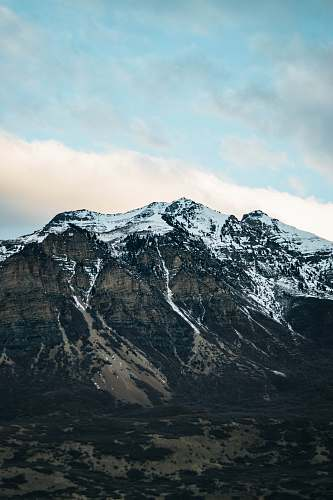 crest snow capped mountain under cloudy sky mountain range