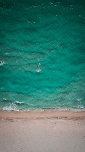 beach aerial photo of green body of water at daytime coast