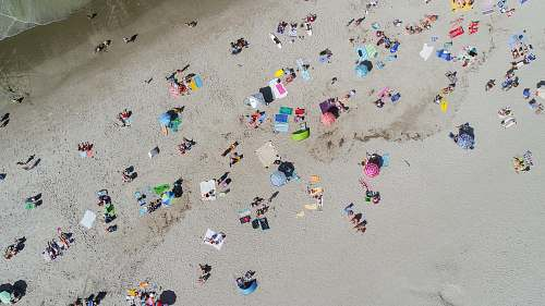 ocean aerial photo of people sunbathing on the beach beach