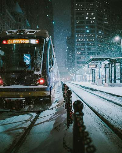 outdoors black and brown train near the building during nighttime snow