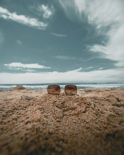 outdoors brown lens sunglasses on sand in low angle photography photography ground