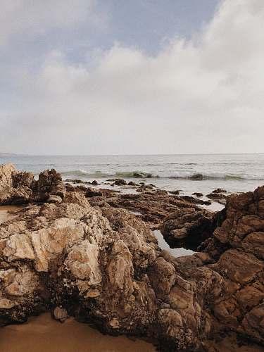 promontory brown rocks beside beach cliff