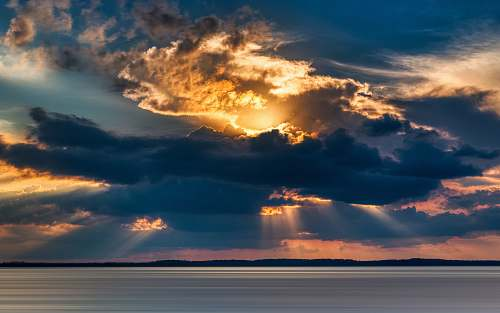 outdoors crepuscular photography of rays from cumulus clouds into the sea sky