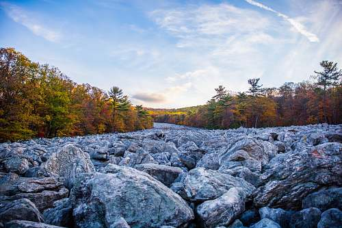 rock gray stones and brown trees under white and blue sky blue rocks family campground