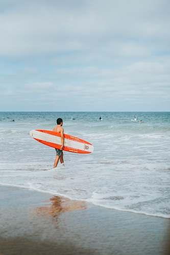 ocean man holding surfboards outdoors