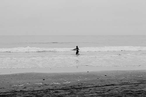 black-and-white man surfboarding at daytime sea