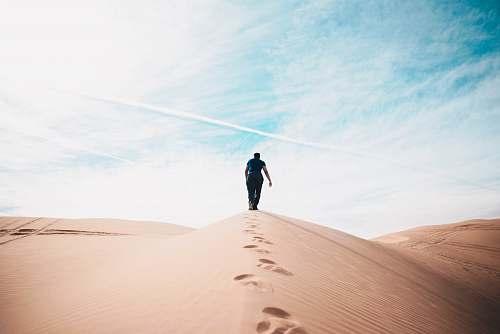 desert man walking on desert dune