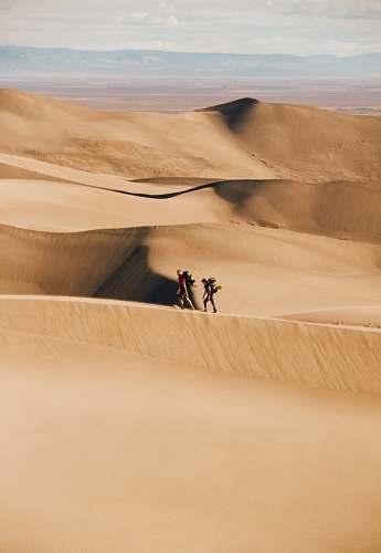 desert people walking in the desert during daytime sand