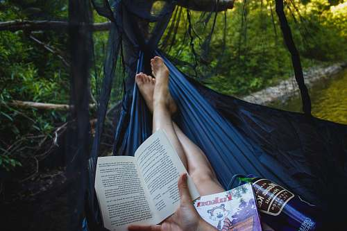 outdoors person holding book hammock