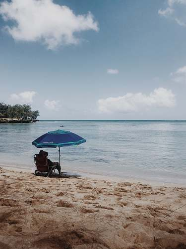 water person sitting on chair under blue umbrella on beach during daytime shoreline