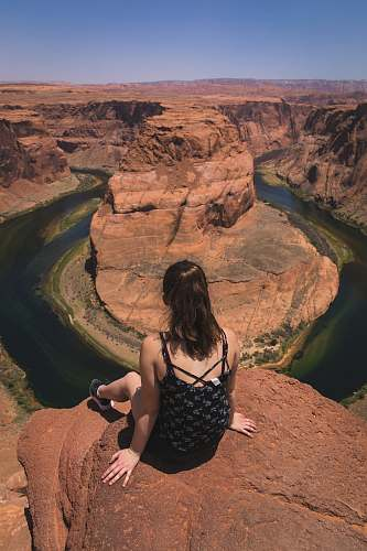 mountain photo of sitting woman in black camisole look down body of water near rocky hills canyon