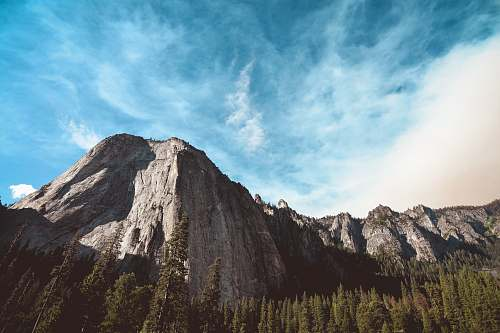 outdoors rock mountain surrounded by pine trees mountain