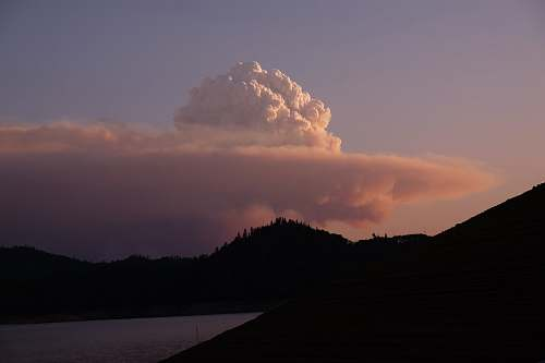 weather silhouette of mountain near body of water during cloudy day outdoors
