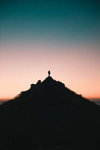 outdoors silhouette of person on top of hill during golden hour sky