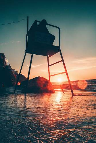 outdoors silhouette photo of person sitting on chair beside sea sunset