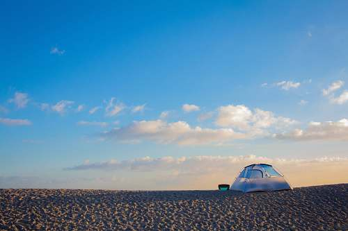 outdoors tent on sand under blue sky and white clouds tent