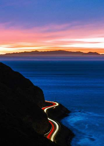 ocean time-lapse photography of cliff road during golden hour malibu