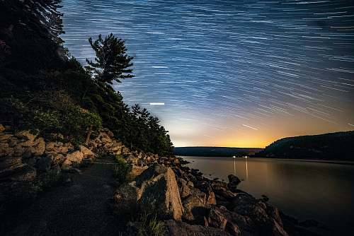 outdoors time-lapse photography of stars above body of water ripple