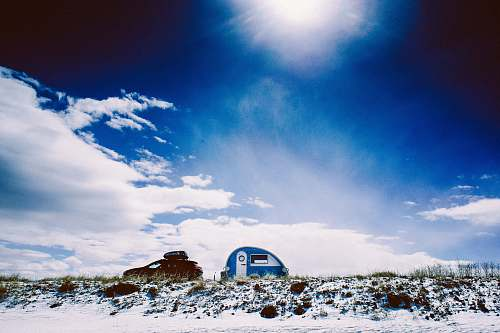 outdoors white and blue trailer under blue calm sky building