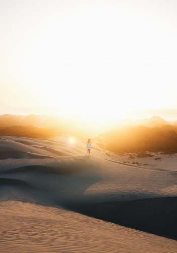 sky woman in white dress standing on sand photo during sunset desert