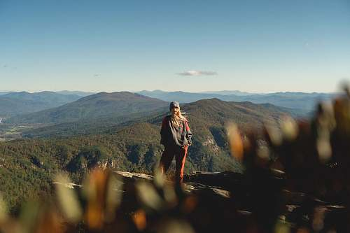 person woman standing on cliff overview of mountain in landscape photography mountain