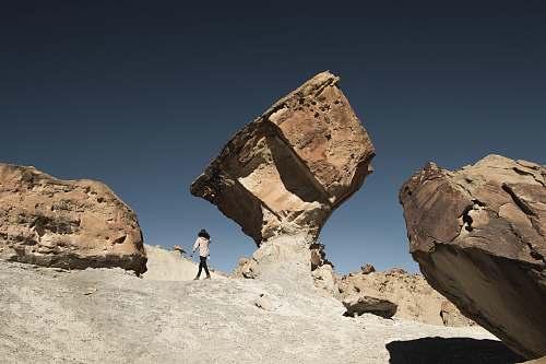 utah woman standing under brown rock formation at daytime rock