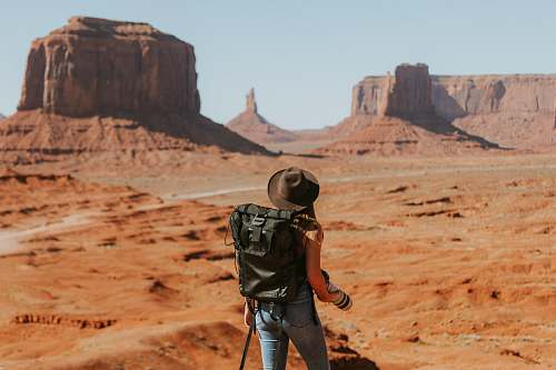 desert woman with black backpack standing on brown dessert outdoors