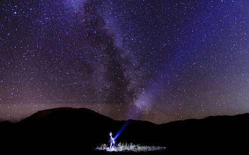 photo astronomy person holding light in milky way galaxy free for commercial use images