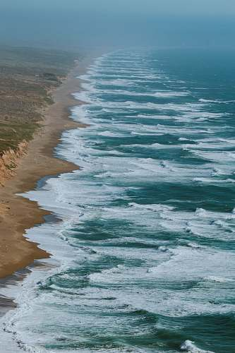 beach aerial photography of ocean waves hitting shore coast