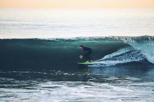 surfing man surfing on sea at daytime water