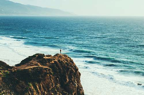 cliff person standing near body of water coast