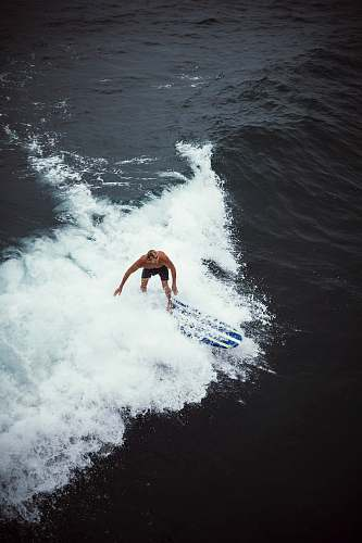 sport person surfboarding on waves surfing