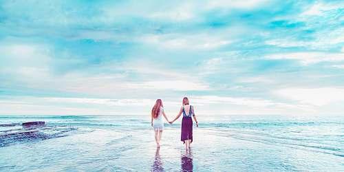 sea two women walking on shoreline holding hands san diego