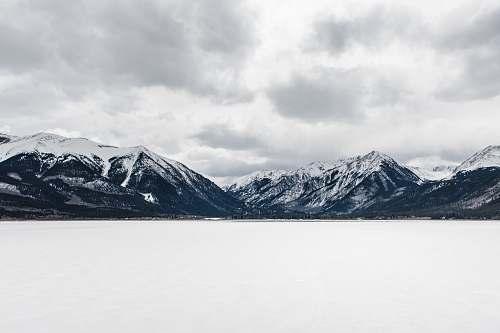 mountain body of water near mountain peak during daytime snow