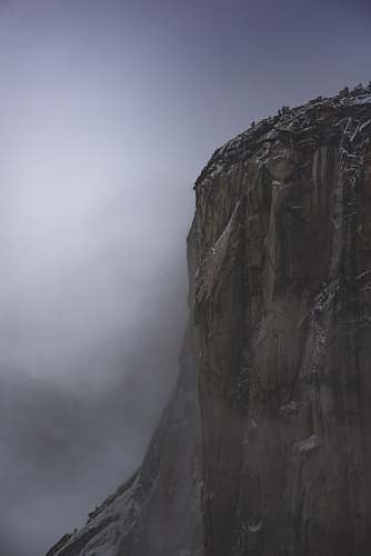 grey brown rocky mountain under white cloudy sky photo cliff