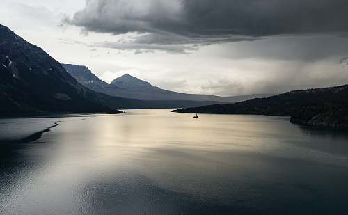 nature calm body of water near mountain under white cloud formation mountain