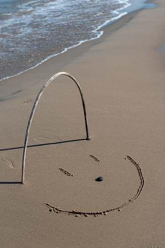 sand grey stick forming u letter on the seashore soil