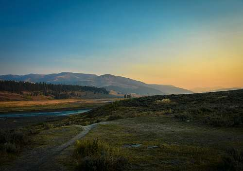 field landscape photography of river and mountain grassland